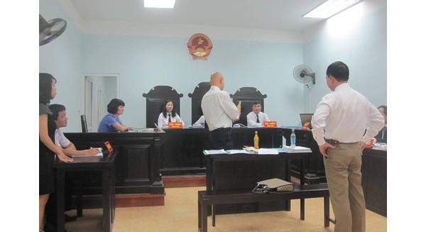 Ảnh: thử nghiệm mở chai, cho vật lạ và đóng lại bằng tay của đại diện Coca-Cola Việt Nam tại phiên tòa sáng 15/9 (báo Gia đình - Xã hội).