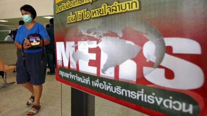 mot phu nu mang khau trang y te ben canh tam bien thong bao cum mers tai vien cac benh truyen nhiem bamrasnaradura o tinh nonthaburi, ngoai o bangkok, thai lan ngay 19.6.2015 - anh: reuters