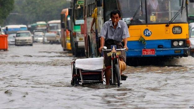 Người dân Myanmar di chuyển trên một con đường ngập nước do lũ lụt  Ảnh:EPA