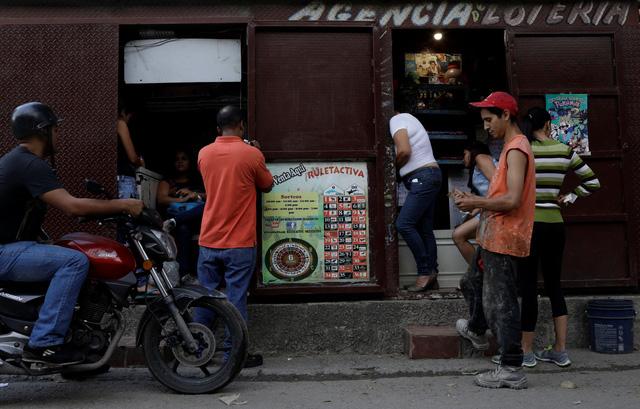 "cuoc khung hoang tai chinh khien nguoi dan venezuela do tien vao cac hoat dong co bac de cau may. trong anh la nguoi dan mua ve tro ca cuoc ""los animalitos"" tai mot cua hang ngoai o caracas - anh: reuters"