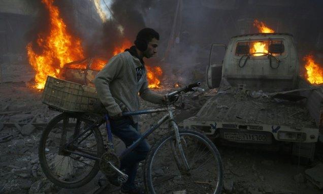 mot nguoi dan nhac xe dap di qua khu bai rac va nhung chiec xe o to dang chay sau cac dot khong kich tai thi tran hamouria cua syria - anh: afp