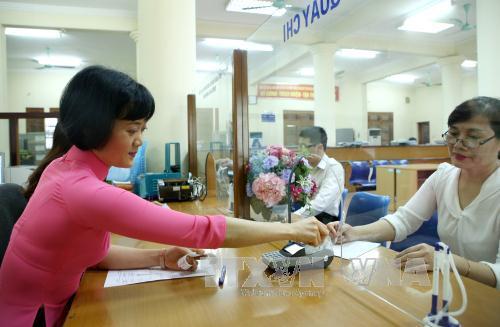 thu ngan sach nha nuoc bang may chap nhan the (pos) tai kho bac nha nuoc quan thanh xuan (ha noi). anh: hoang hung/ttxvn