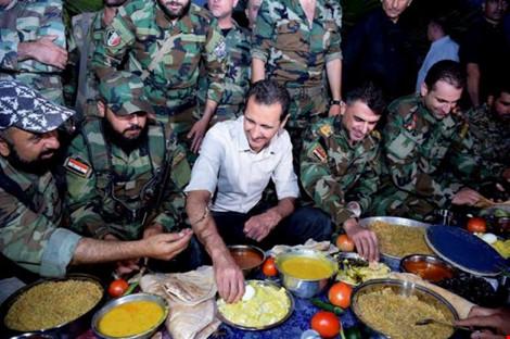 """tong thong syria bashar al-assad (ao trang) cung binh si nuoc nay trong bua """"xa chay"""" (iftar) cua nguoi hoi giao. anh: reuters"""
